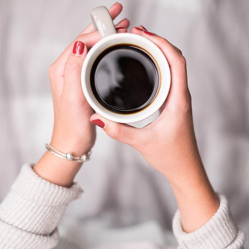 Hand mit Kaffee und Kaffeetasse von Hochland Kaffee