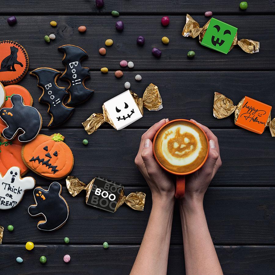 Hände mit Kaffee neben Halloween Süßigkeiten