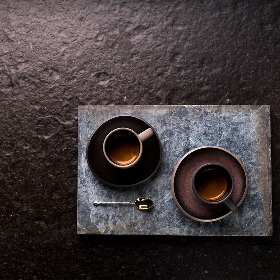 Zwei Hochland Espresso-Tassen auf dunklem Untergrund
