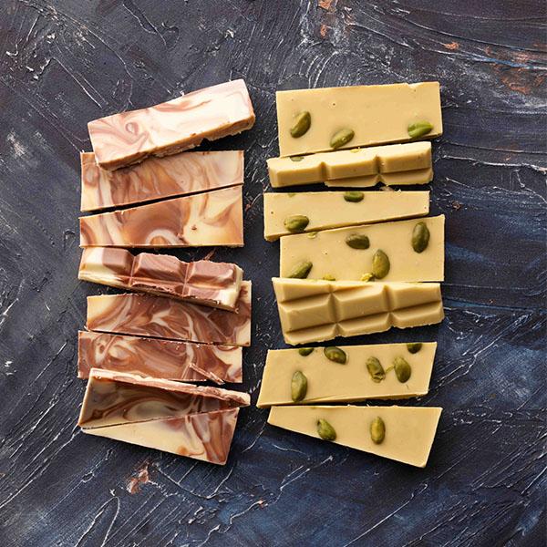 Handgeschöpfte Hochland Schokolade mit Pistazien und Cappuccino auf dunklem Hintergrund