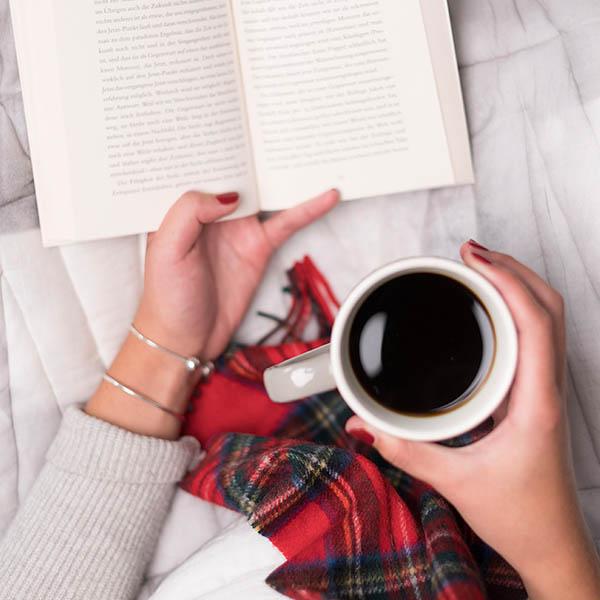 Hochland Kaffee Tasse in Hand mit roter Decke