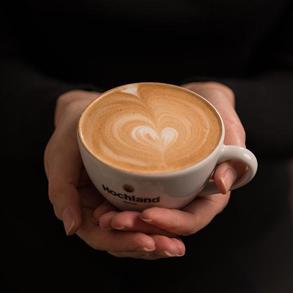 Hochland Kaffee Tasse mit Barista Latte Art in Händen