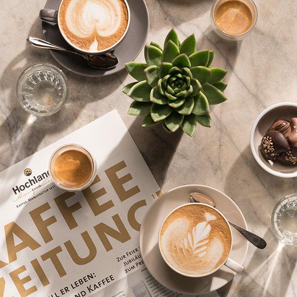 Kaffeezeitung und Hochland Tassen auf Marmortisch