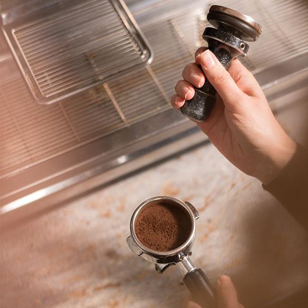 Hände mit Espresso Tamper von Hochland Kaffee