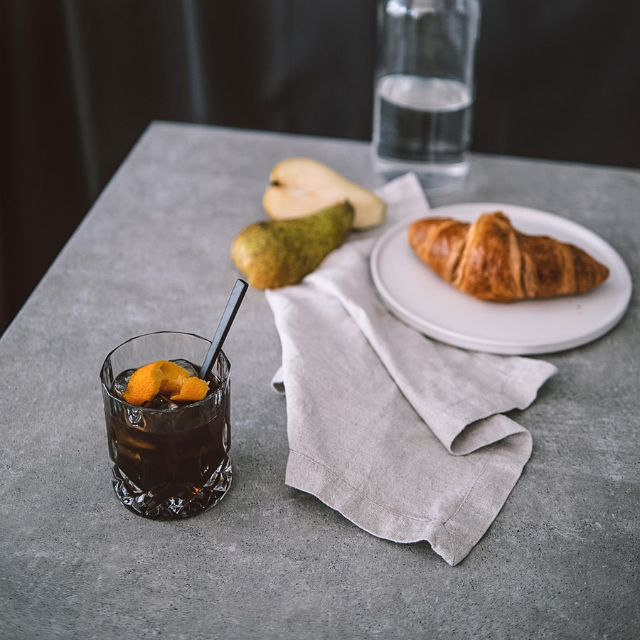 Hochland Cold Brew in Glas mit Orange und Birne auf Marmortischplatte
